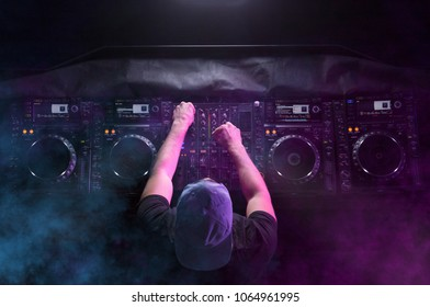 Charismatic disc jockey at the turntable. DJ plays on the best, famous CD players at nightclub during party. EDM, party concept. Top view. Aerial view.