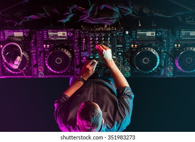 Charismatic disc jockey at the turntable. DJ plays on the best, famous CD players at nightclub during party.