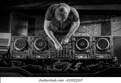 Charismatic disc jockey at the turntable. DJ plays on the best, famous CD players at nightclub during party. Black and white photo.