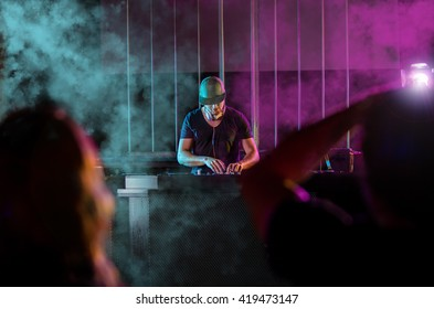 Charismatic disc jockey at the turntable. DJ plays on the best, famous CD players at nightclub during party. EDM party concept.