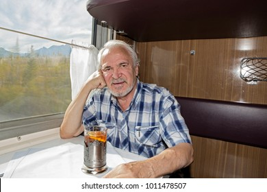 A charismatic elderly man drinking tea in a railway train coupe. Views of the mountains and valleys from the train window.