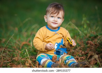 charismatic little baby sitting on the grass in the park outdoors