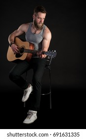 A charismatic man with a beard, playing an acoustic guitar, on a black isolated background