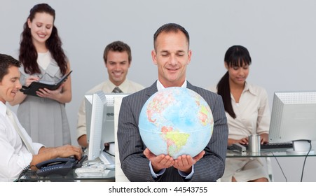 Charismatic manager smiling at global expansion with his team in the background