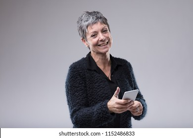 Charismatic older woman with a sweet smile holding a mobile phone in her hands as she looks at the camera over grey with copy space