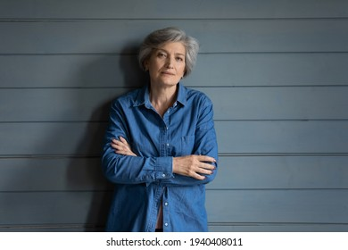 Charismatic person. Serious elderly latin lady posing for portrait keep arms crossed. Confident old female mother grandma in stylish jeans jacket stand by grey planked wall look at camera. Copy space - Shutterstock ID 1940408011