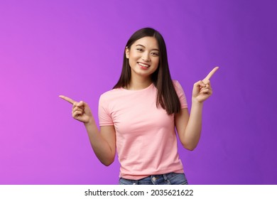 Charismatic relaxed cute asian woman short haircut pointing sideways introduce variety choices, showing left and right products, smiling joyfully, easily making decision, stand purple background