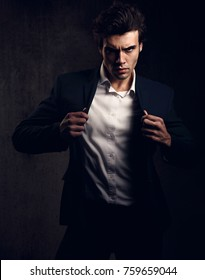 Charismatic sexy male model posing and holding the fashion suit and white style shirt looking energetic on dark shadow background. Closeup toned portrait