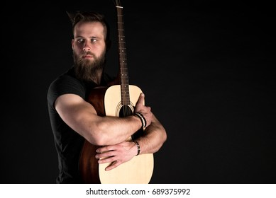 A charismatic and stylish man with a beard holds an electric guitar in his hand on a black isolated background