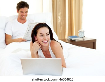 Charismatic woman using laptop lying on her bed