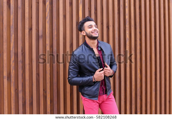 Charismatic Young Businessman Muslim Man Comes Closer to Camera, Smiles and Poses For Camera on Photographer, Shows Gestures, Laughs, Advertises Clothing on Wooden Panel Background Stairs Outdoors