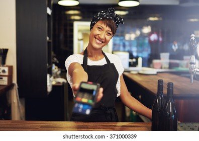 Charismatic young female small business owner requesting payment form a client holding out a handheld banking machine to process their credit card, focus to her face and warm friendly smile