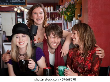 Charismatic young hipster with three female friends at a cafe