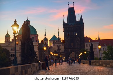 Charles Bridge at dawn: silhouettes of Old Bridge Tower, churches and spires of Old Prague on a sunrise