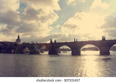 Charles' Bridge and the old town in Prague seen from the river, on a sunny day. Image filtered in faded, washed out, retro style with lens flare; nostalgic, vintage travel concept. Cityscape.