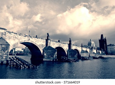 Charles' Bridge and the old town in Prague on a sunny day in black and white. Monochrome image filtered in retro, vintage style with soft focus and red filter; nostalgic concept of travel.