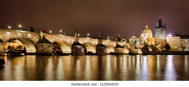 Charles Bridge, The Old Town Bridge Tower, and the St. Francis of Assisi Church, lit up at night - Prague, Czech Republic