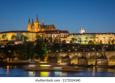 Charles bridge, Prague castle and St. Vitus cathedral in evening view taken from Vltava riverside