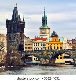 Charles Bridge in Prague, Czech Republic and other historical buildings during the day, cloudy sky at the background