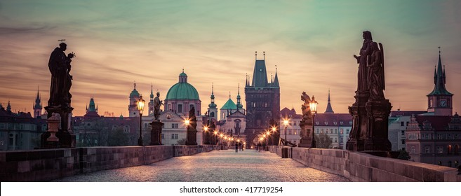 Charles Bridge at sunrise, Prague, Czech Republic. Dramatic statues and medieval towers. Unique panoramic view at dawn when there are almost no people on the bridge.