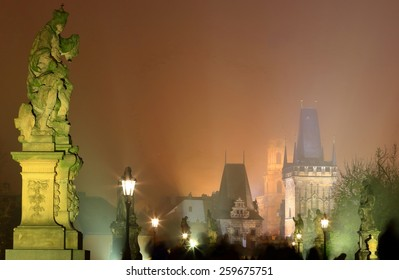 Charles bridge with tourists walking between rows of ghostly statues in foggy night, Prague, Czech Republic