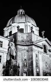 Charles IV statue and Church of Saint Francis of Assisi in Prague, Czech republic. Night scene. Religious architecture. Travel destination. Black and white photo.