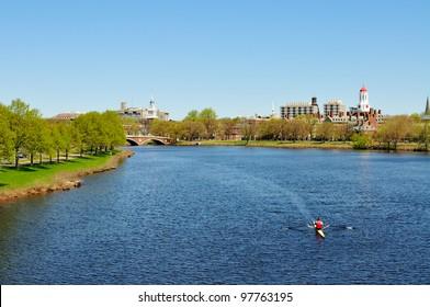 Charles River in the spring. People rowing, jogging, walking� Harvard University buildings in the background.