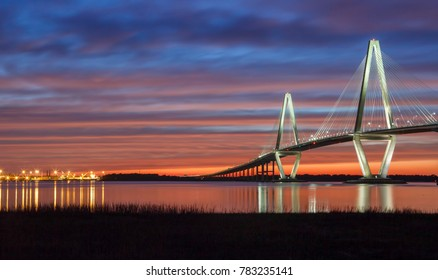 Charleston SC Harbor at sunset with the Ravenel Bridge illuminated and reflecting in the water of Cooper River.