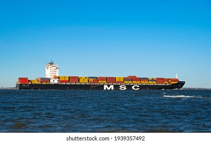 CHARLESTON, SC, USA - MARCH 19, 2021: Leigh, a 275-meter container ship owned by Mediterranean Shipping Company, sails into Charleston Harbor. Photo taken from Sullivan's Island.