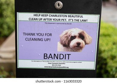 """CHARLESTON, S.C./U.S.A. - JULY 26, 2018: A photo of a pet cleanup sign on a black lockbox sponsored by """"Bandit"""" the dog, located at Waterfront Park in the downtown area."""