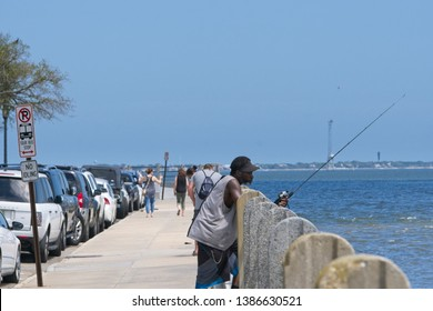 Charleston, South Carolina - May 01 2019: African American man fishing from the Battery in the Charleston harbour with tourist walking past him.