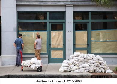 CHARLESTON, SOUTH CAROLINA - SEPTEMBER 12, 2019: Two workers ready sandbags in preparation of Hurricane Dorian.