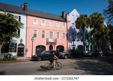 "CHARLESTON, South Carolina/U.S.A. - JULY 29, 2018: A photo of a man biking by the colorful Georgian-style houses on Bay Street's Georgian-style ""Rainbow Row."""