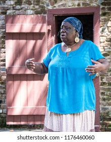 """CHARLESTON, South Carolina/U.S.A. - JULY 29, 2018: A photo of a Gullah storyteller performing on """"Slave Street,"""" a row of preserved brick slave lodgings on the Boone Plantation."""