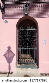 """CHARLESTON, South Carolina/U.S.A. - JULY 29, 2018: A photo of an arched doorway with wrought iron gate on a pink house on Bay Street's Georgian-style """"Rainbow Row"""" of houses."""