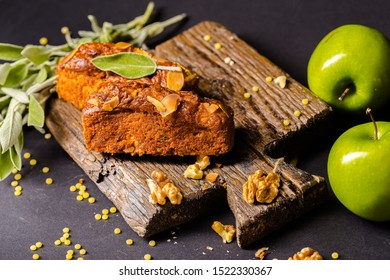 charlotte cake cheesecake rectangular brick lies on a vintage wooden kitchen board, with mint leaves, walnut and green apple, peeling from above, side, isolated on black dark background