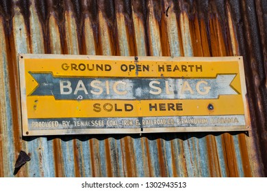 Charlotte, NC, February 2, 2019 - Faded sign for Basic Slag on rusted corrugated metal at old country store
