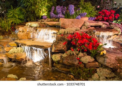 CHARLOTTE, NC - February 23, 2018: Brightly lit waterfall and pond landscape feature on display at the Southern Spring Home & Garden Show.