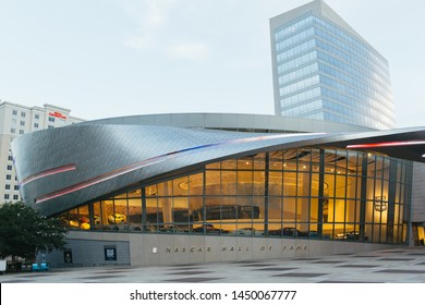 Charlotte, NC - July 4, 2019: Nascar Hall of Fame building front with glass windows with display of some vintage and famous cars on display.