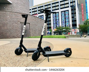 Charlotte, NC - July 8, 2019: Two bird scooters parked by the library in downtown. Popular electric scooters for tourists and locals alike.