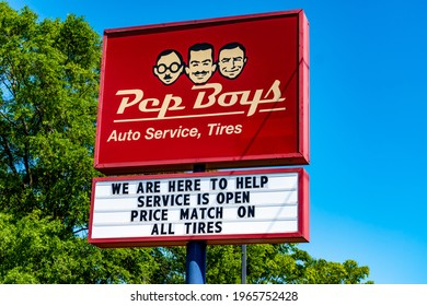 """Charlotte, NC USA - 04 27 2021:  Horizontal, medium shot of """"Pep Boys"""" auto service free standing sign showing brand and logo in bright red and white with green trees and clear blue sky in background."""
