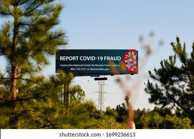 """""""Charlotte, NC / USA - April 9 2020: Billboard promoting a COVID-19 Fraud hotline for those who may be victims of fraudulent activity during the Corona Virus pandemic"""""""