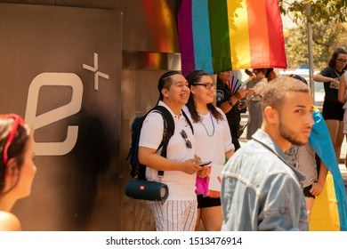 Charlotte, NC / USA - August 18, 2019: Cheerful friends standing under a pride flag in front of the Epicenter at the 2019 Bank of America Charlotte Pride Parade in Charlotte, NC