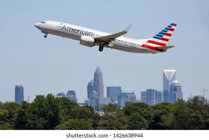 CHARLOTTE, NC (USA) - June 14, 2019:  An American Airlines Boeing 737 commercial jet takes off from Charlotte-Douglas International Airport with the Charlotte skyline in the background.