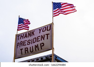 """""""Charlotte, NC / USA - March 2 2020: Two american flags attached to a sign that reads """"Thank You President Trump"""" in red font"""""""