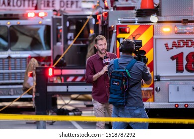 Charlotte, NC / USA - September 30 2019: News reporter covering a fire that erupted in a restaurant at the intersection of E Trade St and N College St in downtown Charlotte near the Epicentre