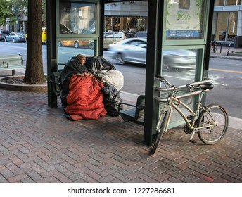 CHARLOTTE, NC, USA-10/30/18:  An apparently homeless woman, with bags of possessions, sleeps at a bus stop on Tryon St.