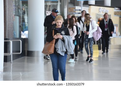 Charlotte, NC/United States- 03/19/2019: An attractive, young woman walks through a terminal at Charlotte Douglas International airport.