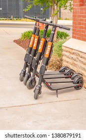 Charlotte, NC/USA - April 17, 2019:  Four urban SPIN transport rental scooters lined up and parked on a sidewalk next to the red brick and white stone wall of an apartment building.
