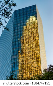 """Charlotte, NC/USA - April 26, 2019: Reflections in glass of  old """"Bank of America"""" headquarters building in the windows of adjacent office tower in uptown Charlotte on a sunny day with sky and trees."""